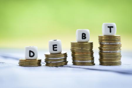 Kości zadłużenia na pieniądze stos monet schody krok w górę / Zwiększone zobowiązania ze zwolnienia konsolidacja zadłużenia koncepcja kryzysu finansowego i problemów ryzyko zarządzanie biznesem oprocentowanie pożyczki