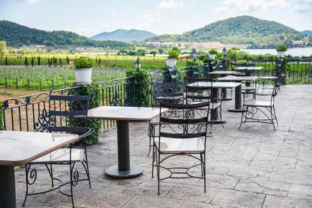 Tisch und Stühle auf dem Balkon des Außenrestaurants mit Blick auf den Naturbauernhof und den Berghintergrund / Esstisch auf der Terrasse