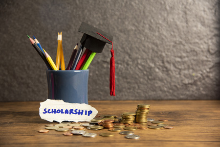 Education and back to school concept with graduation cap on pencils colour in a pencil case on dark background  scholarships with money coin wooden table Imagens