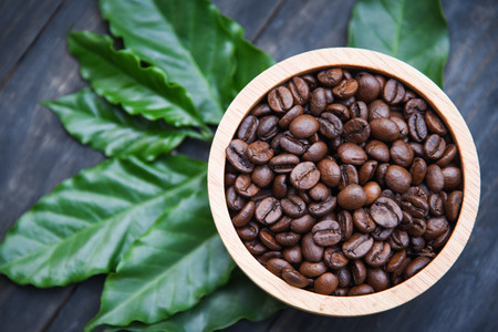 Roasted coffee beans on wooden bowl with green coffee leaf on dark background - top view Foto de archivo - 122758109