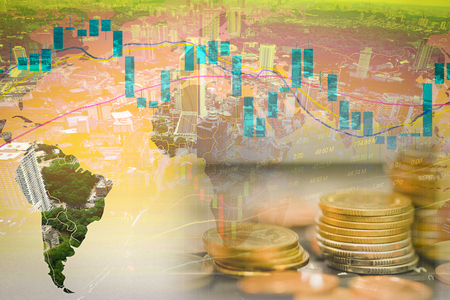 Business graph chart of stock market investment trading on world map double exposure of coins for finance and city building top view background Stock Photo