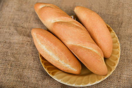 bread and buns assortment / Fresh Bakery bread various types on plate with sack background / homemade breakfast food concept Banque d'images