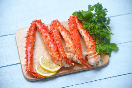 Alaskan King Crab Legs Cooked on wooden cutting board with lemon parsley / red crab hokkaido seafood served table