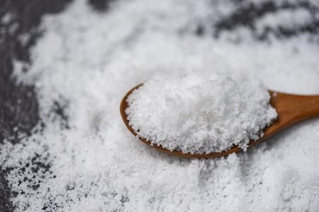 Salt in wooden spoon and heap of white salt on dark background