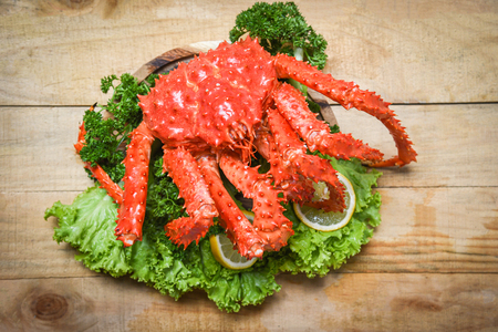 Alaskan King Crab Cooked steam or Boiled seafood and lettuce salad vegetable with wooden background / red crab hokkaido