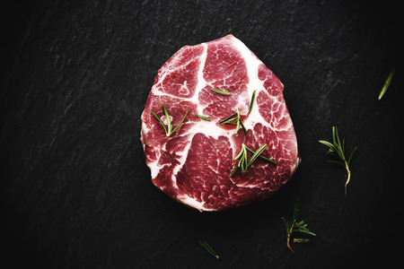 Raw pork meat  Fresh steak ready for grill with spices rosemary on black background - Top view Stock Photo