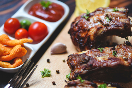 bbq pork ribs grilled with tomatoes ketchup and herbs spices served on the table  Roasted barbecue pork spare rib sliced