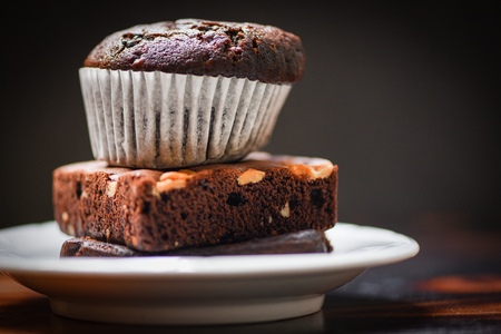 chocolate cupcake on the Chocolate Brownie on white palte with dark background