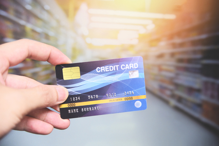 credit card shopping in the supermarket  hand holding credit card payment Banco de Imagens