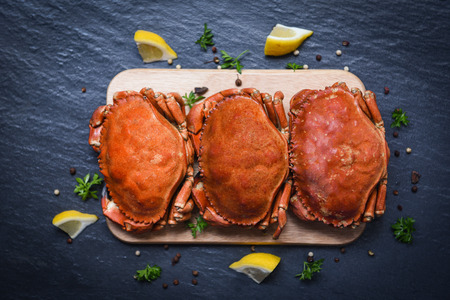 Cooked crabs on wooden board with lemon on plate served on dark plate top view / stone crab steamed seafood
