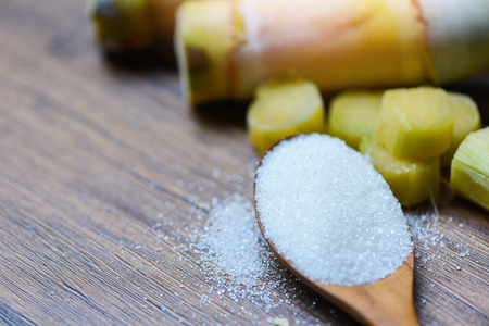 White sugar spoon and sugar cane on wooden table Imagens