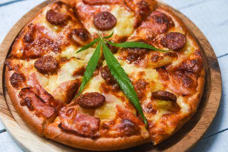 jedzenie konopne z pizzą na drewnianej tacy i widokiem z góry z liści bazylii chilli / pyszny smaczny fast food włoski tradycyjny ser do pizzy z mozzarellą , wędzoną kiełbasą wieprzową , szynką ananasową liść marihuany