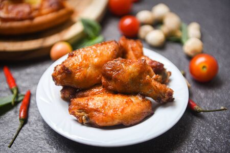 Baked chicken wing bbq grill on plate  hot and spicy chicken and sauce on dark background