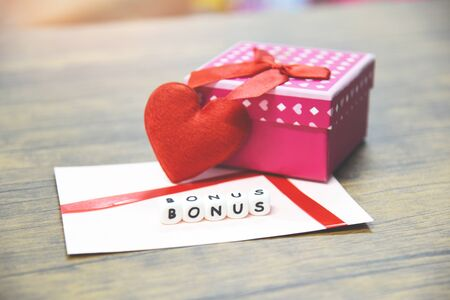 Yearly Bonus concept  card bonus in paper envelope with Gift Box surprise and Red heart for Encouragement Morale in table office company Stock Photo