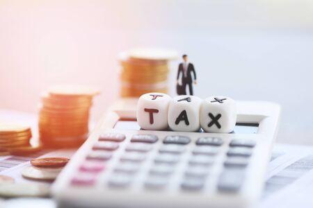 Concetto fiscale e calcolatrice monete impilate sulla fattura cartacea per il tempo di riempimento delle tasse pagate il pagamento del debito in ufficio finanze dell'uomo d'affari Archivio Fotografico