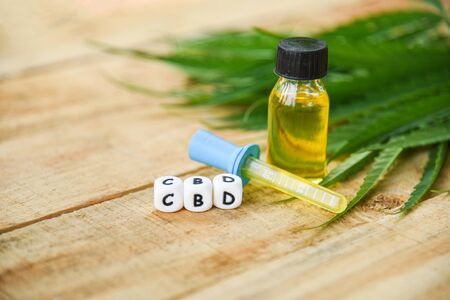Cannabis oil on bottle products wooden background - CBD oil extract from cannabis leaf Marijuana leaves for Hemp medical healthcare natural selective focus