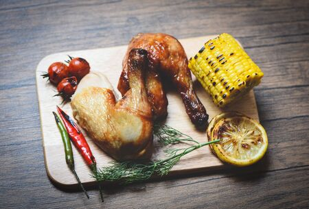 Roasted chicken legs on wooden cutting board with corn lemon chilli spicy herbs spices and tomato on dining table food  Grilled Chicken 写真素材