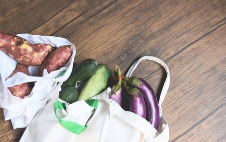 Zero waste use less plastic concept  Fresh vegetables organic in eco cotton fabric bags on wooden table - white tote canvas cloth bag from market free plastic shopping