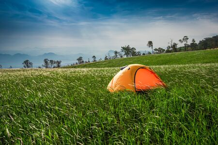 Camping tent tourist on hill mountain landscape green grass meadow on slope hill 写真素材