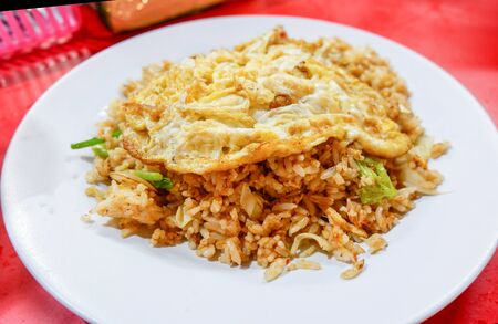 fried rice with omelet on top on white plate