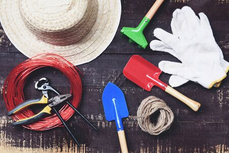 Gardening tools on dark wooden background with pliers , straw hat , rope , gloves trowel garden equipment on top view