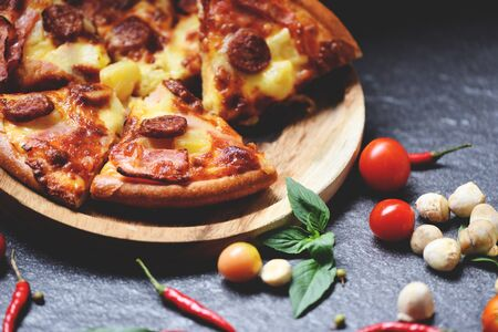 Pizza slice on wooden tray and tomato chilli basil leaf on the dark  delicious tasty fast food italian traditional pizza cheese with Mozzarella , Smoked pork sausage , Pineapple ham on topping sauce