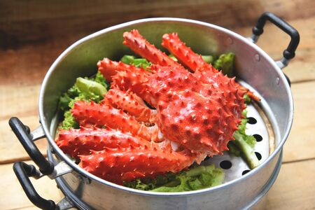 Alaskan King Crab Cooked steamer food on steaming pot seafood and lettuce vegetable on wooden background  red crab hokkaido