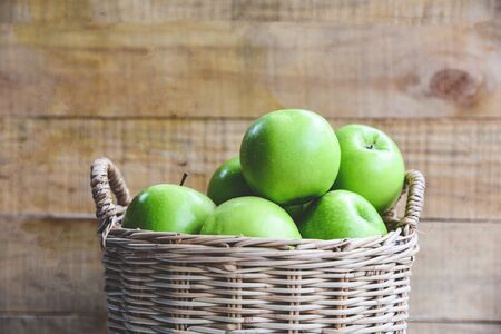 Green Apples  Harvest apple in the basket on wooden background