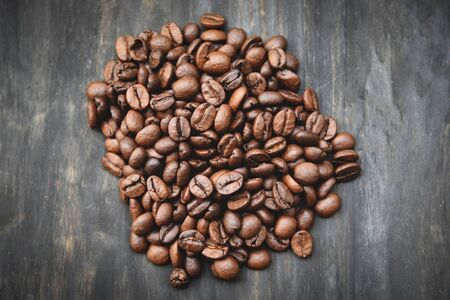 Coffee beans roasted on rustic wood background