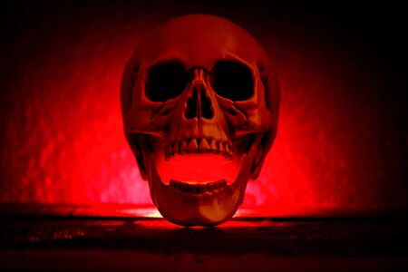 Human Skull with red light on dark black background , Halloween decorations concept