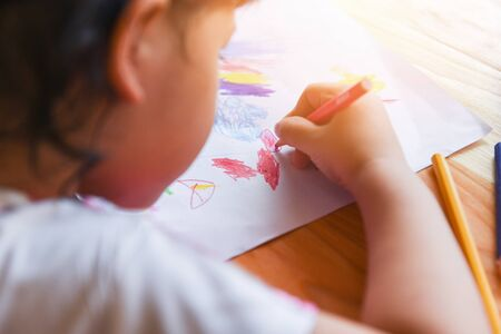Girl painting on paper sheet with colour pencils on the wooden table at home / child kid doing drawing picture and colorful crayon