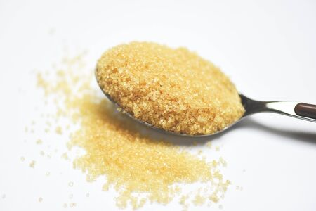 brown sugar in a spoon on white background , close up Stock fotó