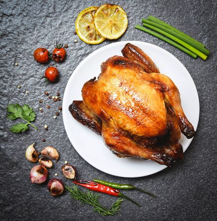 Roasted chicken on plate / baked whole chicken grilled with on herbs and spices and dark background