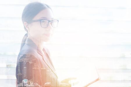 business woman success in suit and eyeglasses / double exposure asian women silhouette lighting effects with city landscape and using technology holding tablet