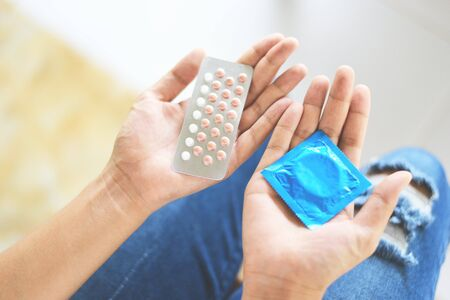 Woman holding contraception pills and condom in hand / Birth control contraceptive means prevent pregnancy or sexually transmitted disease Stock Photo - 127480309