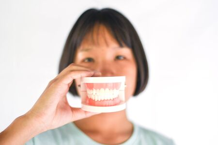 Dental health and child brush teeth concept  Asian child girl holding dental prosthesis , dentures for study