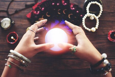 Psychic readings and clairvoyance concept / Crystal ball fortune teller hands and Tarot cards reading divination , with effect filter blur selective focus Archivio Fotografico