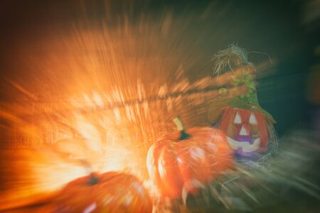 Halloween pumpkin lantern with dry straw on wooden / head jack o lantern evil faces spooky holiday decorate on halloween background with effect filter blur