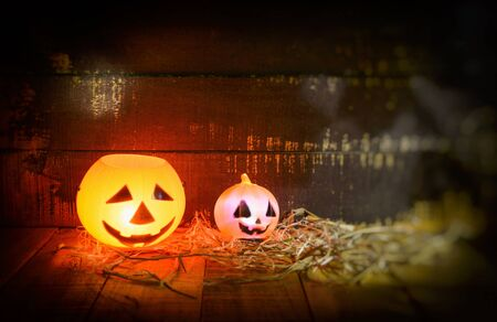 Halloween pumpkin lantern with dry straw on wooden / head jack o lantern evil faces spooky holiday decorate on halloween background