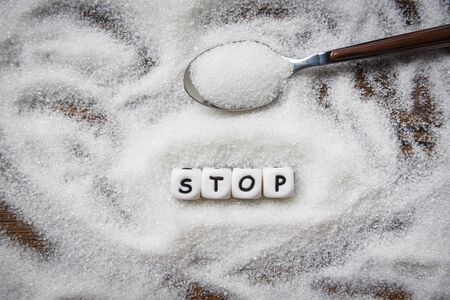 no sugar stop text blocks with white sugar on spoon wooden background / suggesting dieting and eat less sugar for health concept