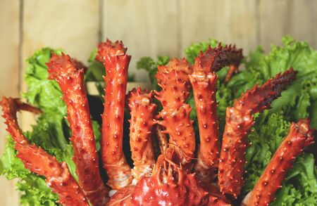Alaskan King Crab Cooked steam or Boiled seafood and lettuce salad vegetable wooden dining table background , top view / red crab hokkaido Stock Photo