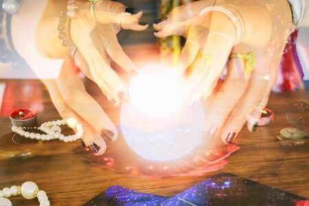 Psychic readings and clairvoyance concept / Crystal ball fortune teller hands and Tarot cards reading divination