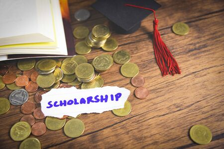 Scholarship for education concept with money coin on wooden with dark background and graduation cap on a open book