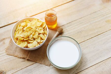 Cornflakes in bowl with milk and honey in jar on wooden background for cereal healthy food breakfast