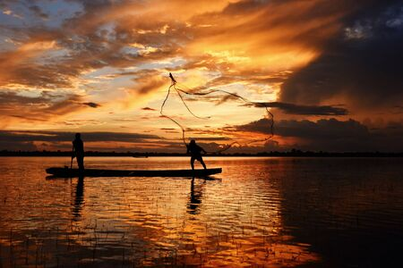 Asia fisherman net using on wooden boat casting net sunset or sunrise in the Mekong river - Silhouette fisherman boat with mountain background life person countryside