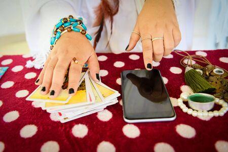 Wahrsagerin liest Glückslinien auf dem Bildschirm Smartphone moderne Horoskope Online-Wahrsagerei-Anwendung Handlesen Psychische Lesungen und Hellsehen-Hände-Konzept mit Tarot-Karten-Wahrsagung