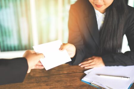 Asian business woman receiving salary bonus money from boss or manager at office happily / Yearly Bonus concept for encouragement morale Foto de archivo