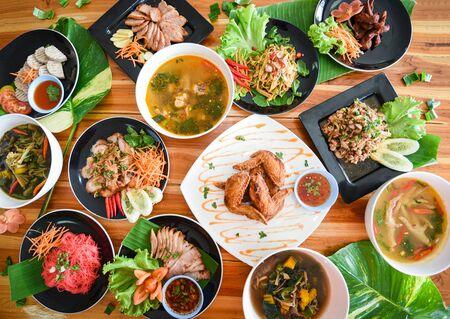 Thailändisches Essen auf dem Esstisch serviert / Tradition nordöstliches Essen Isaan köstlich auf Teller mit frischem Gemüse - Viele verschiedene thailändische Menüs asiatisches Essen auf einem Holztisch, Draufsicht Standard-Bild