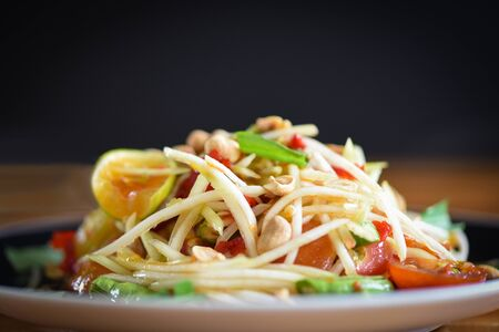 Papaya salad served on plate with dark background / Close up of green papaya salad spicy thai food on the table selective focus - Som tum Thai Asian food