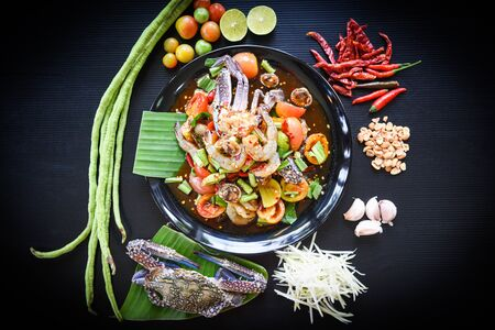 Seafood salad spicy with fresh shrimp crab cockles served on black plate fresh vegetables herbs and spices ingredients with chilli tomato peanut garlic green papaya shredded - Som tum Thai menu Asian